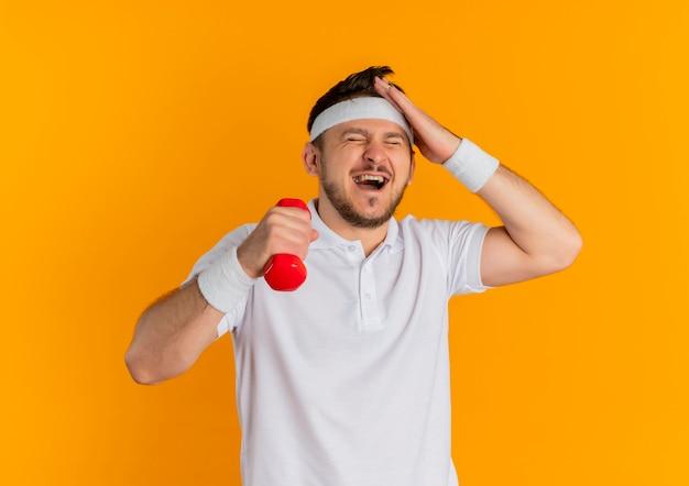 Jonge fitness man in wit overhemd met hoofdband uit te werken met halter op zoek verward, vergat staande over oranje muur Gratis Foto
