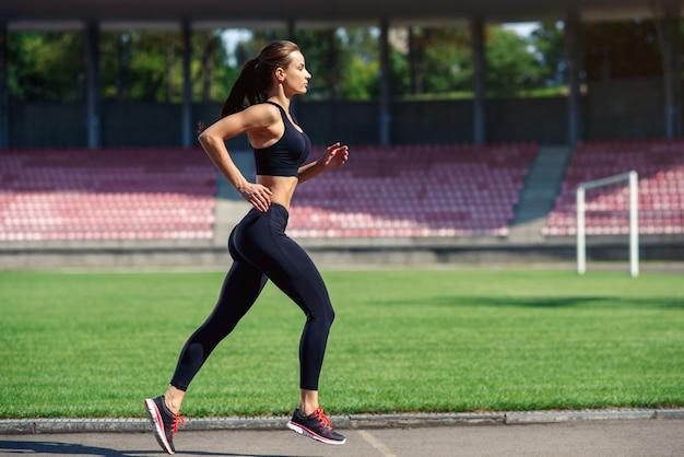 Jonge fitness vrouw die op een stadionspoor loopt Premium Foto