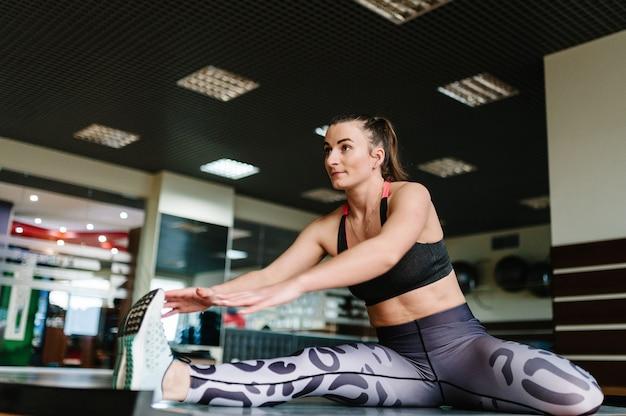 Jonge fitness vrouw doen rekoefeningen en zittend op een mat in de sportschool. Premium Foto