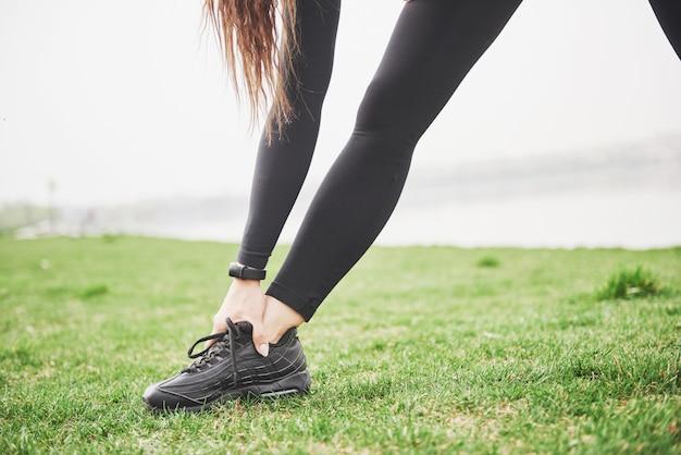 Jonge fitness vrouw loper benen strekken voordat uitgevoerd op park Gratis Foto