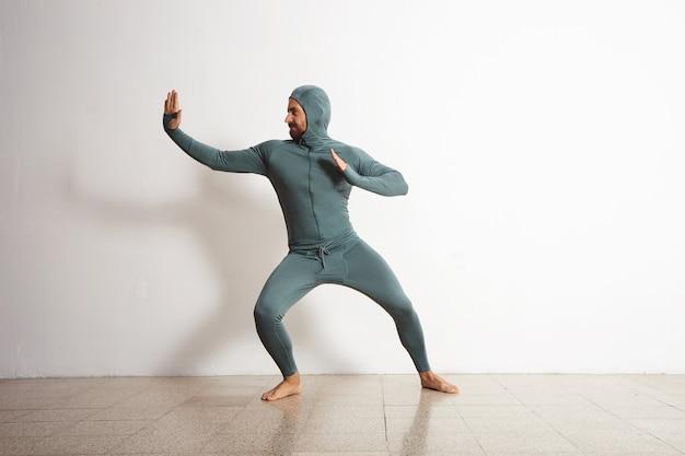 Jonge, fitte, bebaarde atleet man draagt zijn winter snowboardint baselayer thermische suite en heeft plezier en gedraagt zich als een ninja Gratis Foto