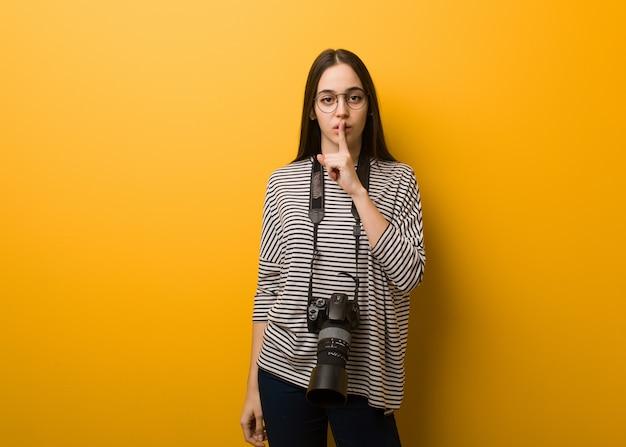 Jonge fotograafvrouw die een geheim houdt of om stilte vraagt Premium Foto
