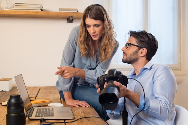 Jonge fotografen die foto's op laptop bekijken. assistent-fotograaf helpt fotograaf bij het selecteren van foto's. jong team van fotograaf die in een professionele studio werkt. Premium Foto
