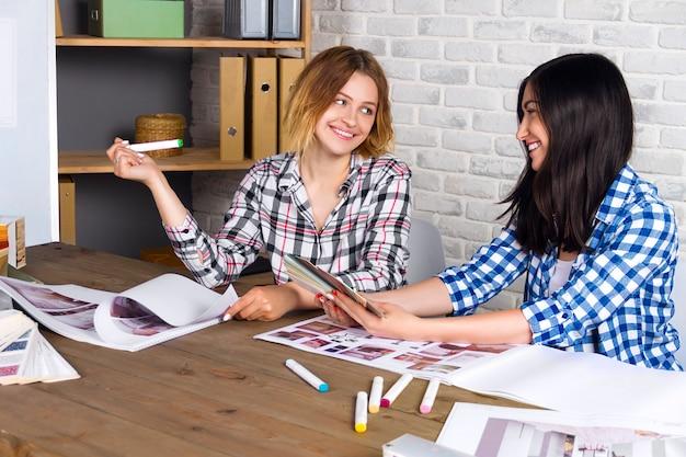 Jonge freelancers interieurontwerpers werken nieuw appartementproject in ontwerpstudio uit. de vrouwelijke vergadering van het twee vrouwenmeisje met ontmoet bureau met speld op schetstekeningen en ontwerpen van nieuw project Premium Foto