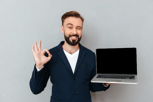 Jonge gebaarde mens die in kostuum camera kijken terwijl het houden van laptop geïsoleerde computer Gratis Foto