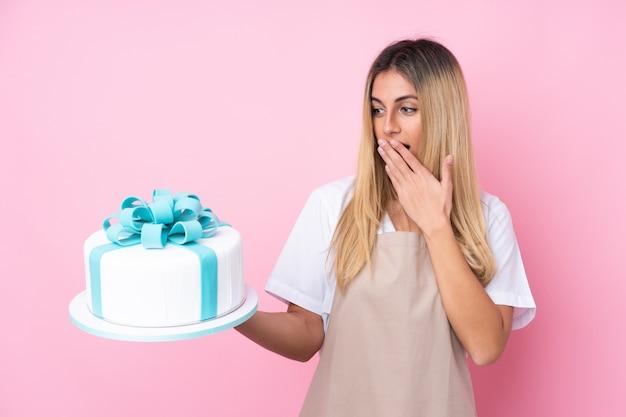 Jonge gebakjevrouw met een grote cake over geïsoleerde roze muur met verrassing en geschokte gelaatsuitdrukking Premium Foto
