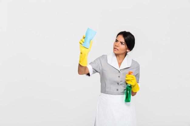 Jonge geconcentreerde meid in uniform schoonmaak venster met doek Gratis Foto