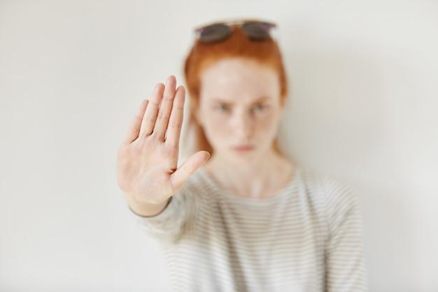 Jonge geërgerde vrouw met een slechte houding die een stopgebaar maakt met haar handpalm naar buiten, nee zeggend, ontkenning of beperking uitdrukkend. negatieve menselijke emoties, gevoelens, lichaamstaal. selectieve aandacht bij de hand Gratis Foto