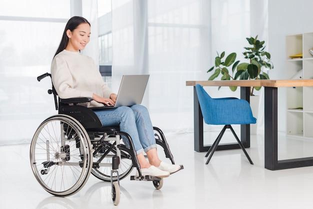 Jonge gehandicapte vrouwenzitting in een rolstoel die laptop met behulp van op het werk Gratis Foto