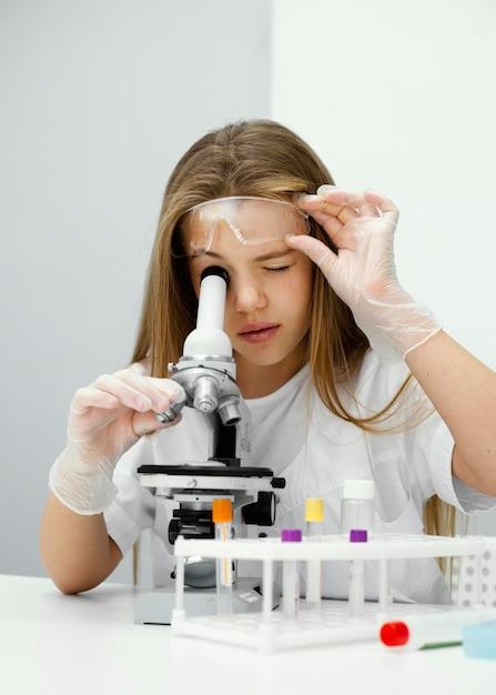 Jonge geïntrigeerde meisjeswetenschapper die microscoop gebruikt Gratis Foto