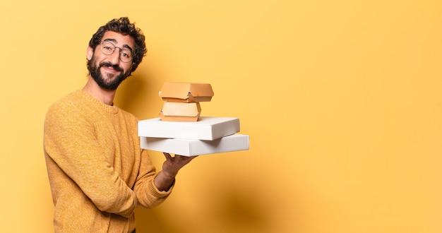Jonge gekke bebaarde man die fastfood met een kopie ruimte heeft weggehaald Premium Foto