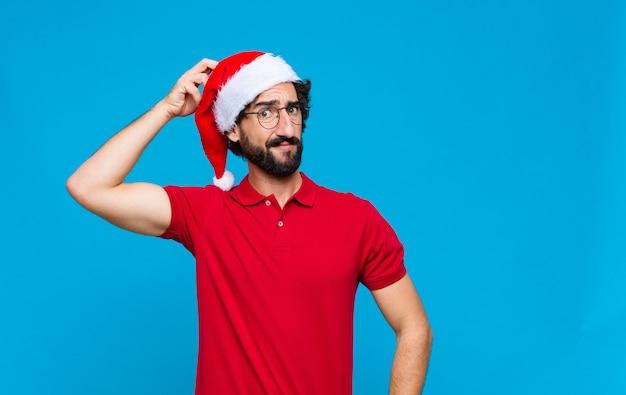 Jonge gekke bebaarde man met kerstmuts. kerst concept Premium Foto