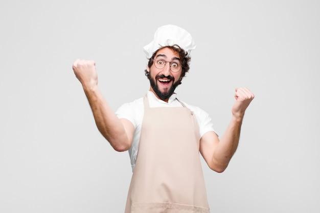 Jonge gekke chef-kok triomfantelijk schreeuwen, ziet eruit als opgewonden, blij en verrast winnaar, vieren over witte muur Premium Foto
