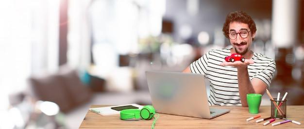 Jonge gekke grafische ontwerper op een bureau met laptop Premium Foto