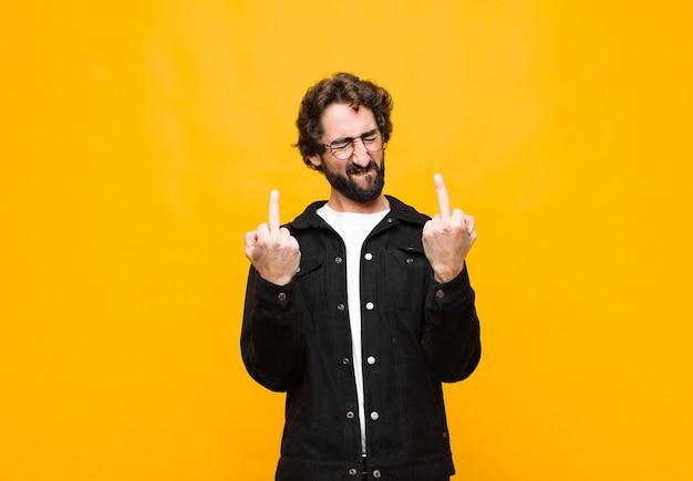 Jonge gekke knappe man die zich provocerend, agressief en obsceen voelt, de middelvinger wegknipt, met een opstandige houding tegen de oranje muur Premium Foto