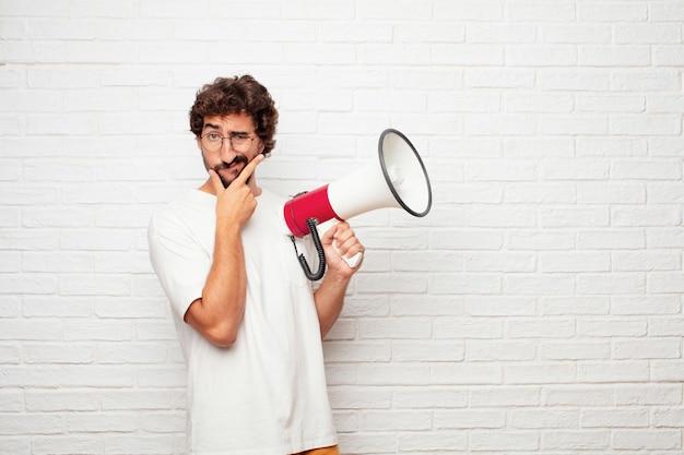 Jonge gekke man met een megafoon tegen de muur. Premium Foto