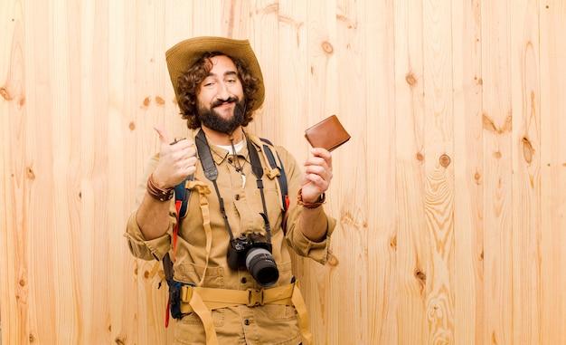 Jonge gekke ontdekkingsreiziger met strohoed en rugzak op houten achtergrond Premium Foto