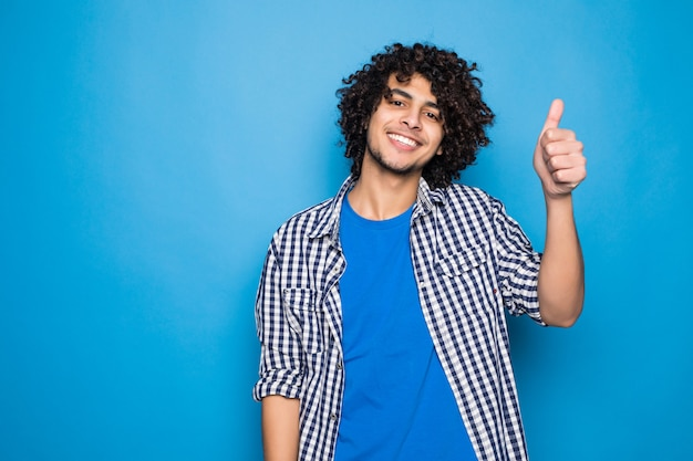 Jonge gekrulde mens met duimen die omhoog op blauwe muur wordt geïsoleerd Gratis Foto