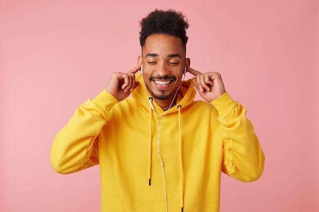 Jonge gelukkig afro-amerikaanse man in gele hoodie, genietend van cool nieuw nummer van zijn favoriete band op koptelefoon Gratis Foto