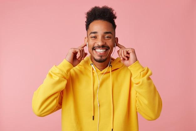 Jonge gelukkig afro-amerikaanse man in gele hoodie, genietend van zijn favoriete coole liedje op de koptelefoon, kijkend naar de cavera en breed glimlachend Gratis Foto