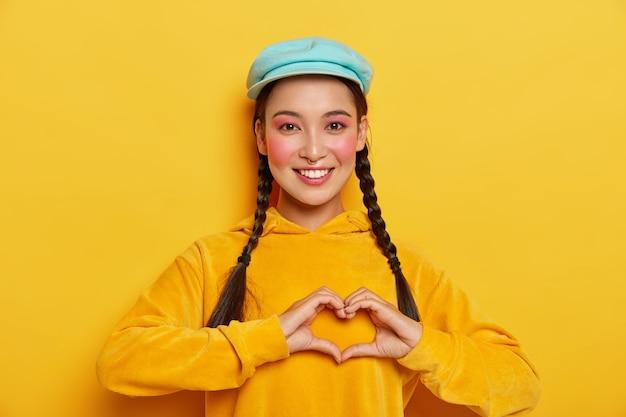 Jonge gelukkig koreaanse vrouw maakt hartgebaar over borst, heeft twee staartjes, draagt blauwe pet en gele hoody, drukt goede emoties uit Gratis Foto