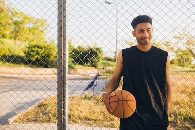 Jonge gelukkig lachend zwarte man sport doen, basketbal spelen op zonsopgang, actieve levensstijl, zomerochtend Gratis Foto