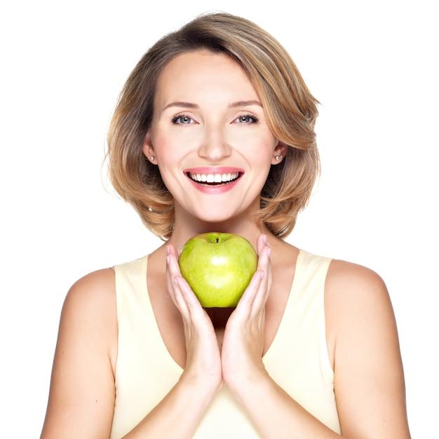 Jonge gelukkig lachende vrouw met groene appel - geïsoleerd op wit. Gratis Foto