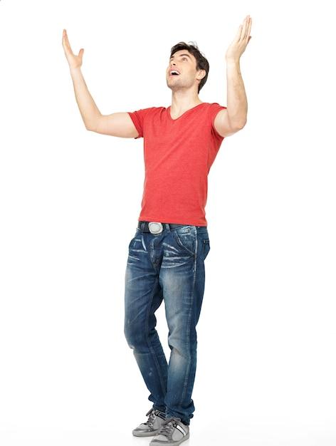 Jonge gelukkig man in casuals met opgeheven handen omhoog geïsoleerd op een witte achtergrond. Gratis Foto