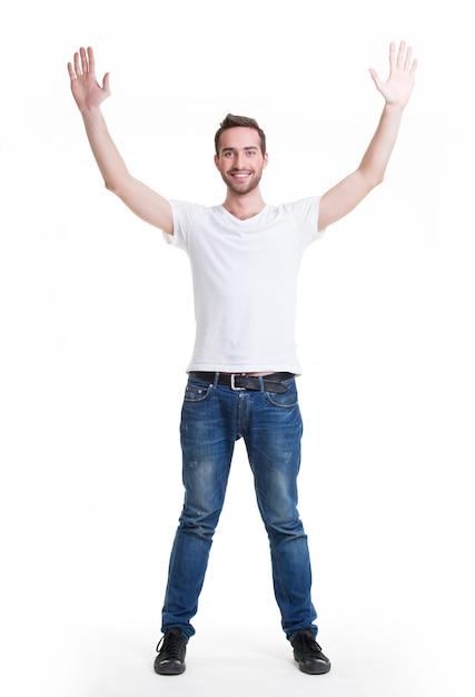 Jonge gelukkig man in casuals met opgeheven handen omhoog - geïsoleerd op wit. Gratis Foto