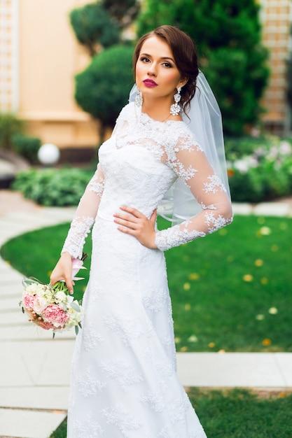 Jonge gelukkig mooie bruid in witte elegante trouwjurk met boeket poseren buiten in park. Gratis Foto
