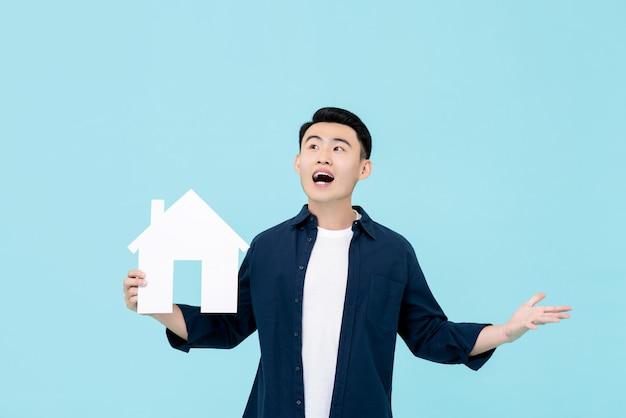 Jonge gelukkige aziatische mens die het huismodel van de verrassingsholding voor bezitsconcepten kijken Premium Foto