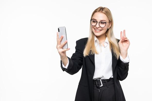 Jonge gelukkige bedrijfsvrouw die telefonisch spreken die aan geïsoleerde vrienden golven Gratis Foto