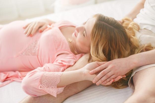 Jonge gelukkige familie die op de baby wacht. man omarmt zachtjes de zwangere vrouw in de slaapkamer. vrouw in afwachting van de geboorte van een kind close-up. 9 maanden zwangerschap Premium Foto