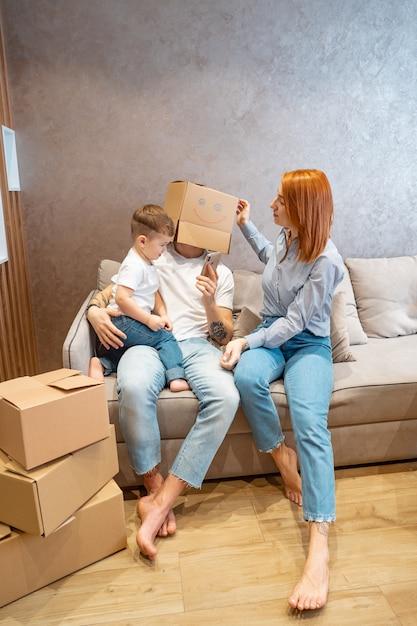 Jonge gelukkige familie met kind uitpakkende dozen die samen op bank zitten Gratis Foto