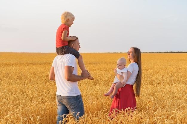 Jonge gelukkige familie wandelen door tarweveld. Premium Foto