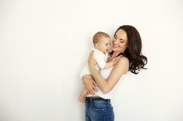 Jonge gelukkige moeder het glimlachen holding die haar babydochter bekijken over witte muur. Gratis Foto