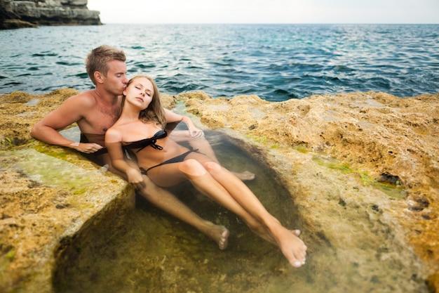 Jonge gelukkige mooie paarvrouw en man die van tijd in natuurlijke rotspool genieten met water met rotsen Premium Foto
