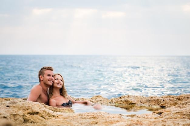Jonge gelukkige mooie paarvrouw en man zitting in natuurlijke rotspool met water en het glimlachen met overzees Premium Foto