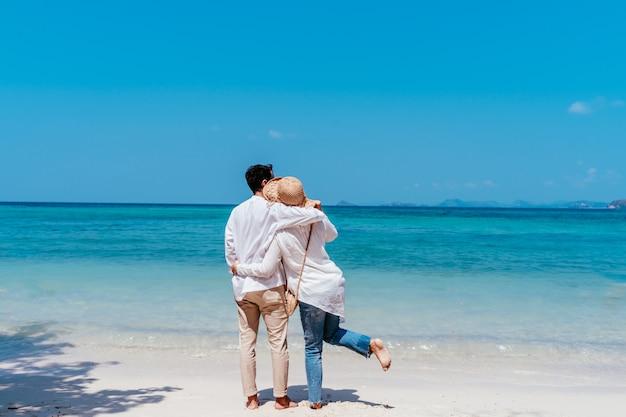 Jonge gelukkige moslimpaar witte kleding op kust. Premium Foto