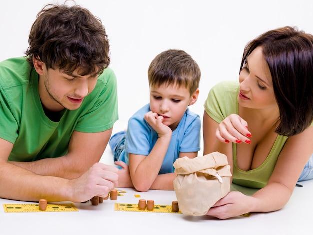 Jonge gelukkige ouders spelen binnenshuis met zoontje Gratis Foto