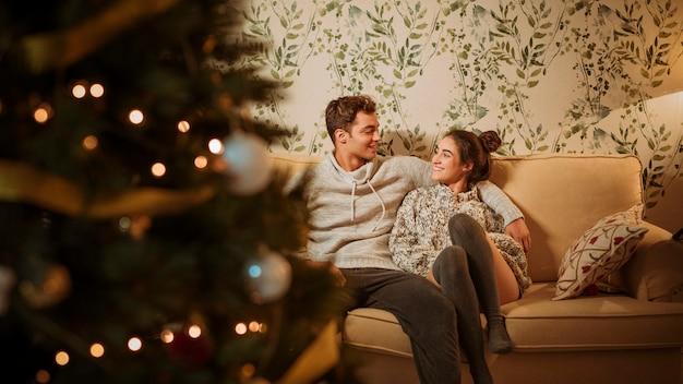 Jonge gelukkige paar zittend op de bank Gratis Foto