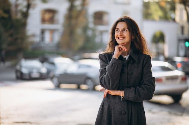 Jonge gelukkige vrouw die in de straat loopt Gratis Foto