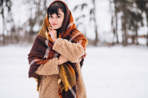 Jonge gelukkige vrouw in warme doeken in een winter park Gratis Foto