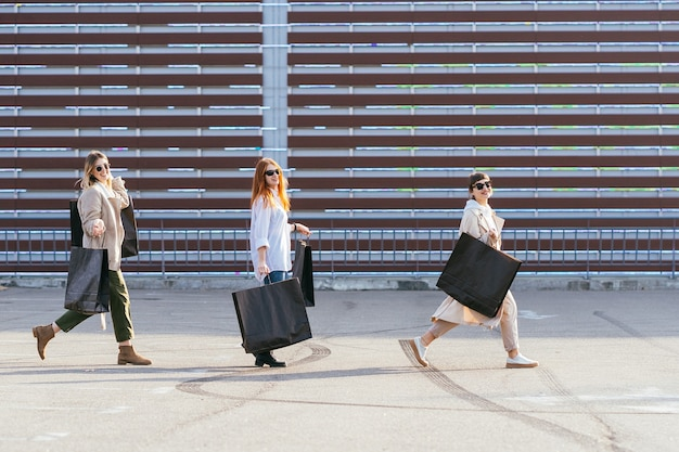 Jonge gelukkige vrouwen met boodschappentassen die op straat lopen. Gratis Foto