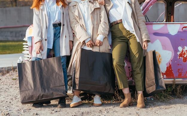 Jonge gelukkige vrouwen met boodschappentassen poseren in de buurt van een oude versierde auto Gratis Foto