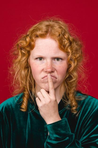 Jonge gember peinzende vrouw grimassen en lippen aan te raken Gratis Foto