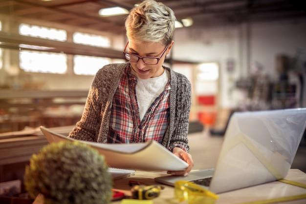 Jonge gerichte vrouweningenieur die sommige projecten in haar workshop bekijken Premium Foto