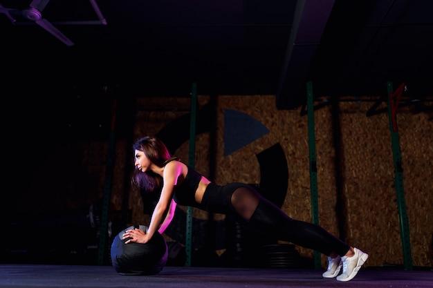 Jonge geschikte vrouw die opdrukoefening of plankoefening op geneeskundebal doen bij gymnastiek Premium Foto
