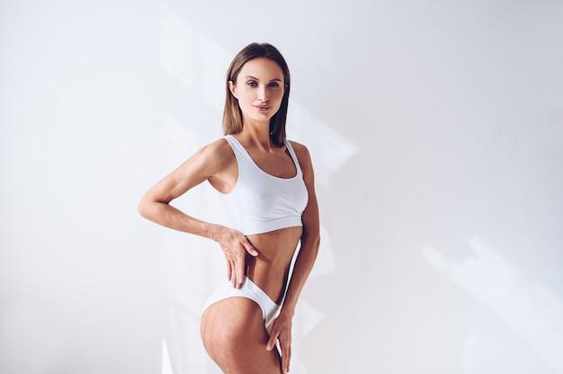 Jonge geschikte vrouw in witte lingerie op witte geïsoleerde muur. gespierde slanke aantrekkelijke vrouw met platte buik. kopieer ruimte voor tekst. lichaamsverzorging, gezond en sportief leven, ontharing, yoga concept Premium Foto