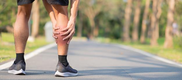 Jonge geschiktheidsmens die zijn verwonding van het sportenbeen houden. spierpijn tijdens training Premium Foto
